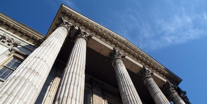 An upward view of a building with pillars.