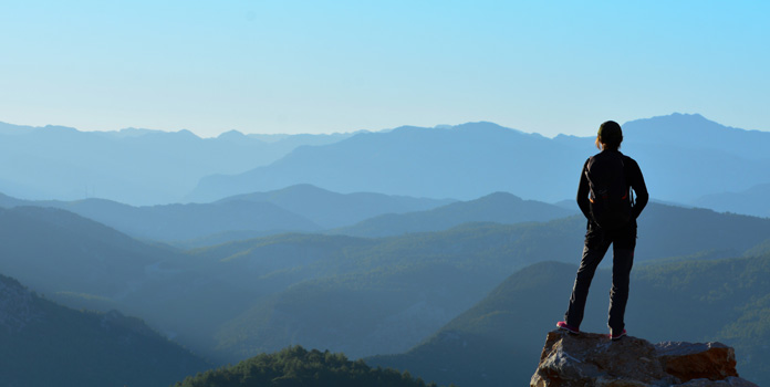 A person standing on top of a rock at the top of a mountain that overlooks distant mountains.