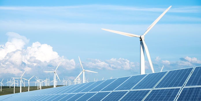 Solar panels in front of a field of wind turbines