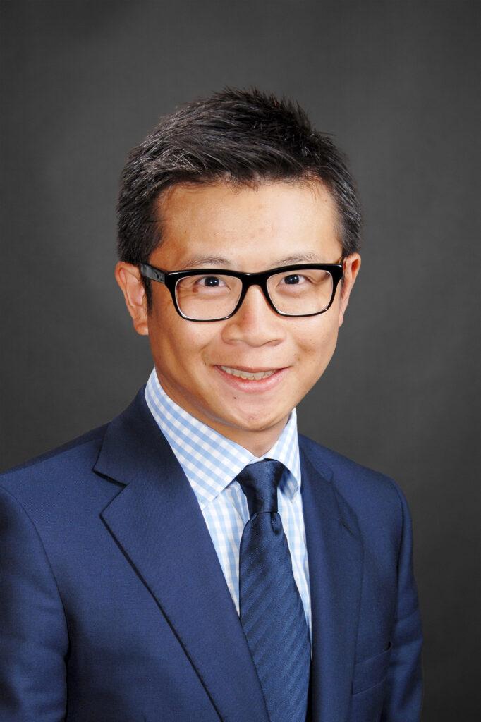 Headshot of Sheldon Chan on a grey background
