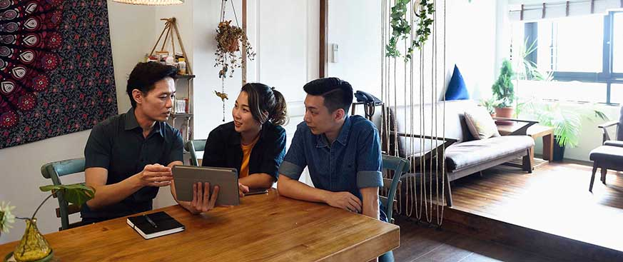 2 Asian men and one Asian woman looking at a tablet at a dinner table in a modern apartment