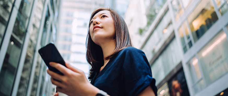 Low angle portrait of confidence and successful young Asian businesswoman with coffee to go, using smartphone while standing against highrise corporate buildings in financial district in the city
