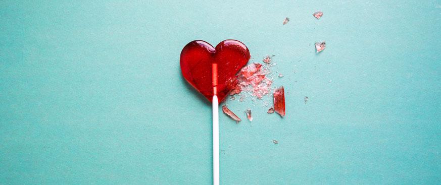 Broken red heart lollipop on an eggshell blue background