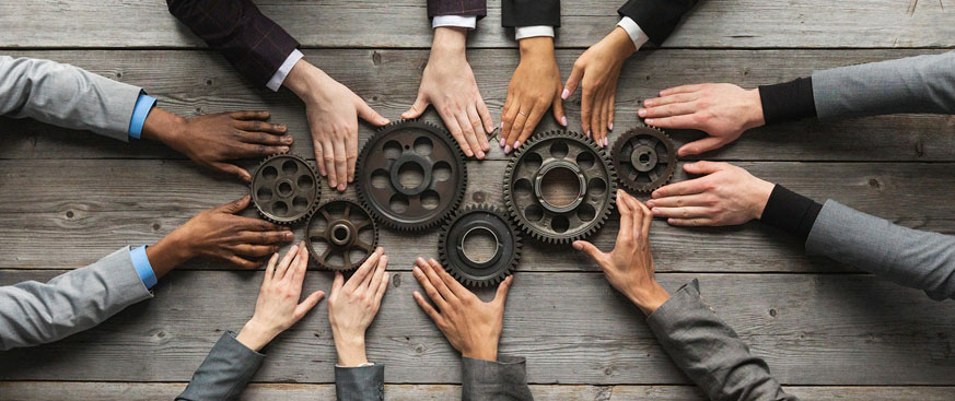 Diverse hands holding gears together