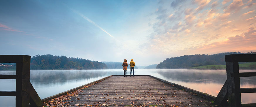 Credit Outlook Hero Image featuring two people standing at the end of a pier, looking out over a lake