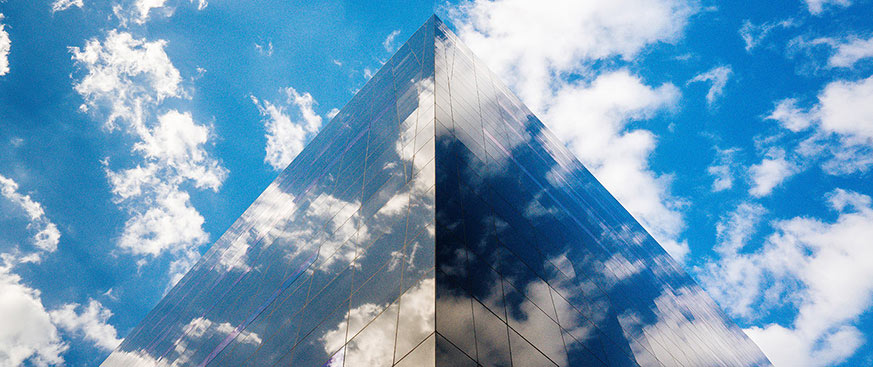 office building reflecting a partly cloudy blue sky